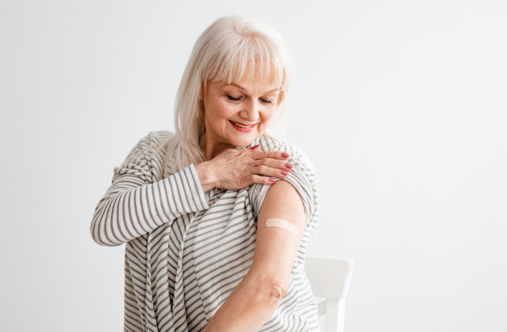 An older woman who has just received her second dose of the Covid-19 vaccine smiling down at the bandage on her arm